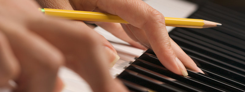 Photo of hands holding a pencil while playing keys of a piano.