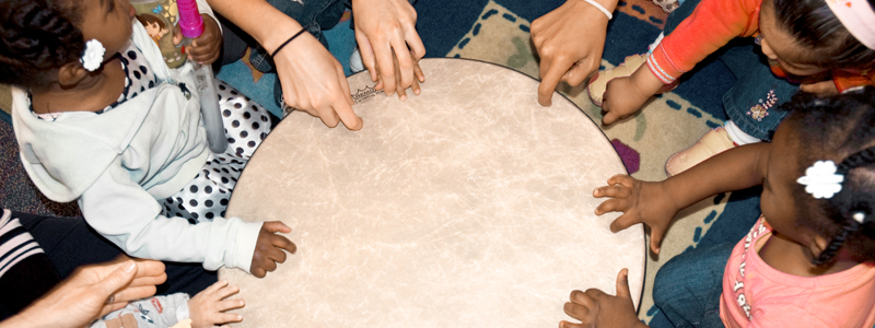 Photo of several toddlers learning to play a musical drum for the first time.