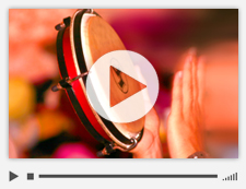 Video slide of hands playing a tambourine.