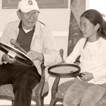 Photo of a Junior Joy Giver and an older adult playing paddle drums together.