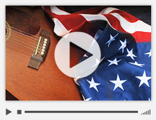 Video slide of an American flag draped over an acoustic guitar.
