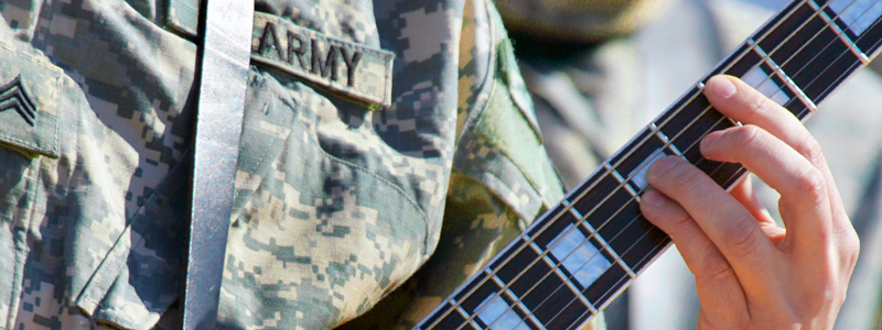 Photo of a man, dressed in US Army camouflage clothing, playing a guitar.